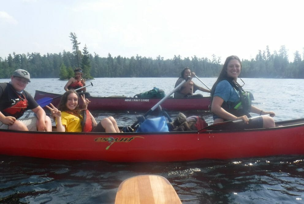 Two canoes on a lake. One with two paddlers, and one with three paddlers.