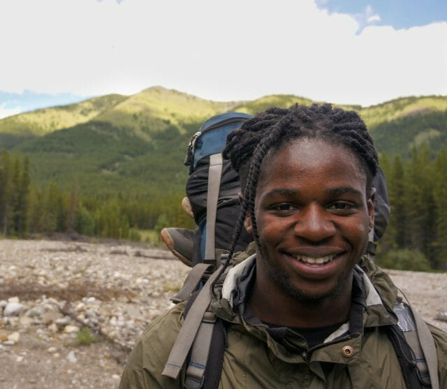 A backpacker smiling with mountains behind them.
