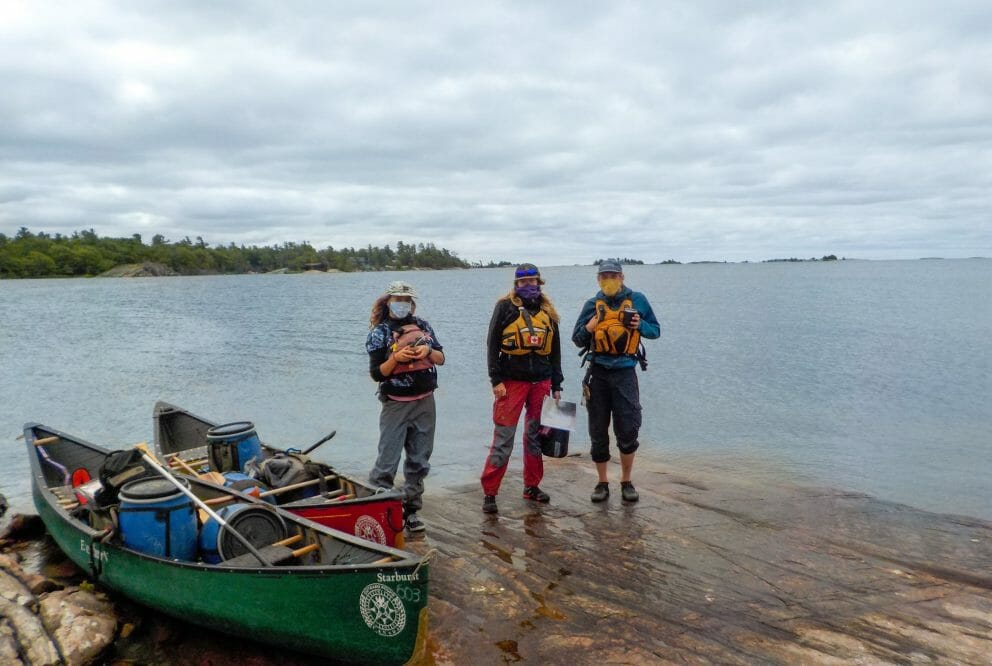 Three instructors in masks and lifejackets standing on the rocky shore of a lake. Two canoes beside them.