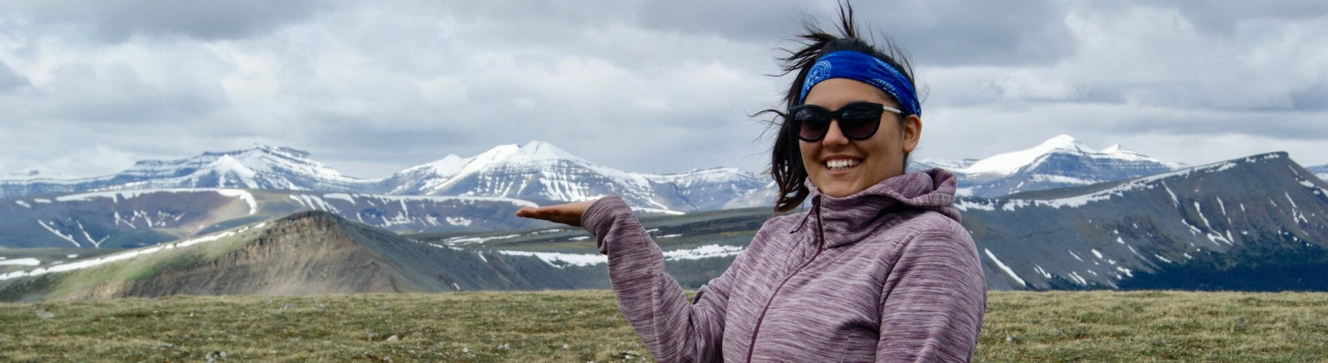 Woman holding out flat of hand to show row of mountains