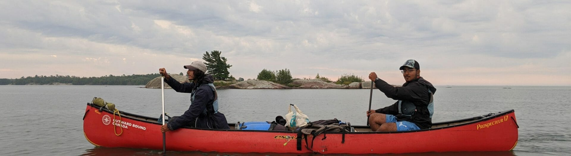 Two people paddling a canoe on a lake with an island in the distance