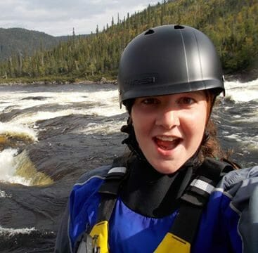 Image of aperson in a helmet in front of white water rapids