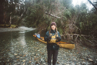 Image of a person standing in front of a canoe