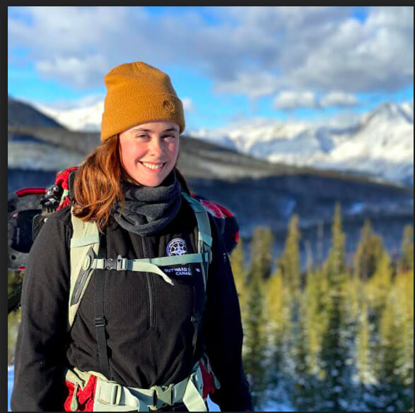 Image of a smiling person in front of a mountain range