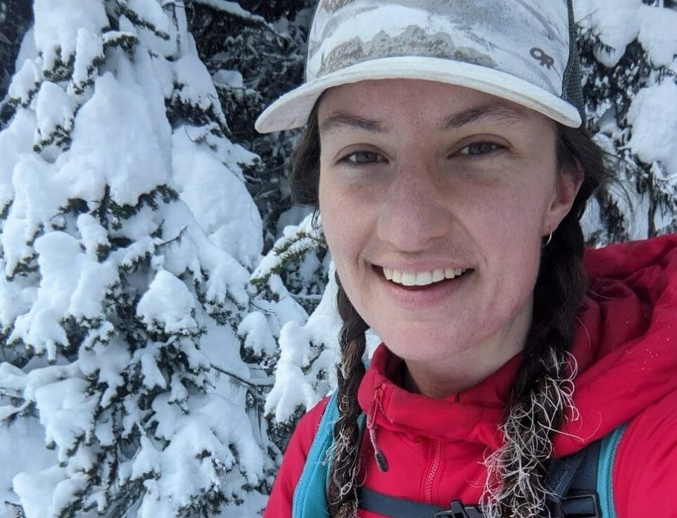 A person smiling with a backpack and snow